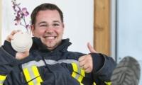 Feuerwehrmann mit Rauchmelder in Schutzkleidung